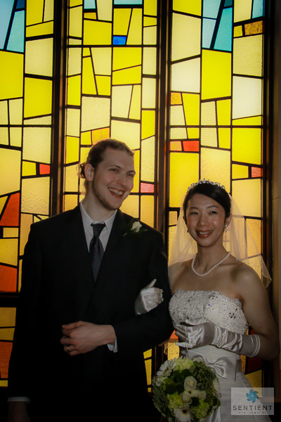 Groom & Bride Against Stained Glass Window