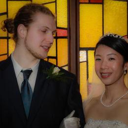 Groom & Bride In Front Of Church Window