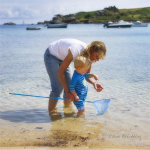 At A small child playing on a beach on the Isles of Scilly,Cornwall with his grandmother at the seaside