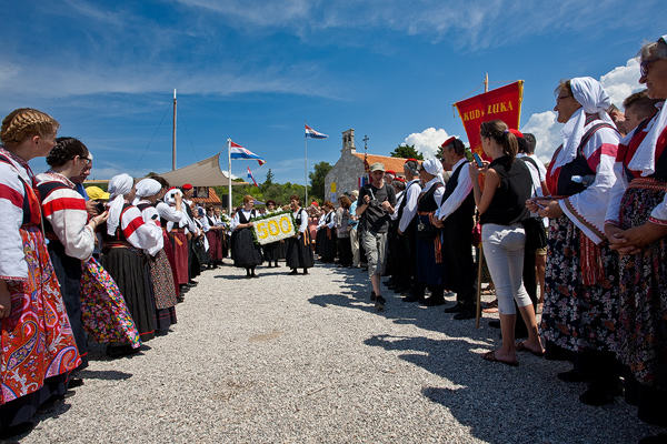 Line of folklor societies during Or Lady of the snow procession in Zdrelac, island Ugljan, Croatia