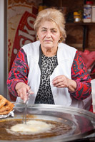 Lady cooking typical domestic food on Samobor town carneval, Croatia