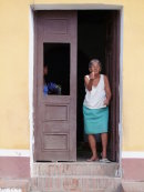 Cuban lady beckoning to enter her house