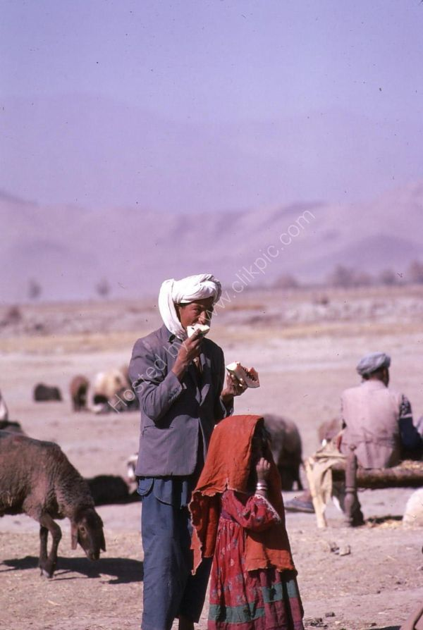 Afghani Farmer & Daughter eating Water Melon, Camel Market, Kabul