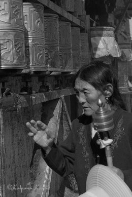 Tibetan woman turning prayer wheels in Lhasa Tibet