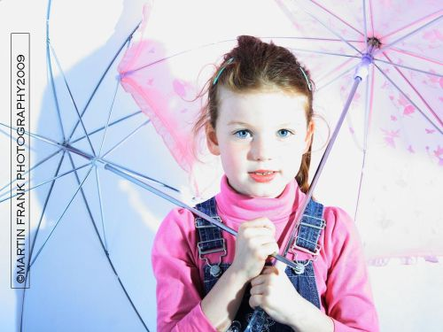 Young girl with blue eyes and umbrellas