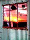 Sunset reflected in broken barn window