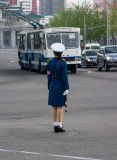 A female traffic officer monitors traffic at every junction.