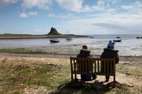 02D-2544 Two People Sitting on a Bench and Enjoying the View of Lindisfarne Castle Across the Ouse From the Harbour at Low Tide Holy Island Northumberland