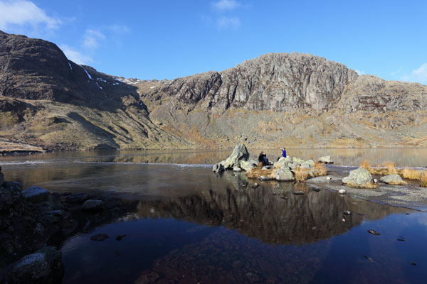03D-0747 Walkers Taking a Break at Stickle Tarn on a Sunny Winters Day With the Mountain of Pavey Ark Behind Lake District Cumbria