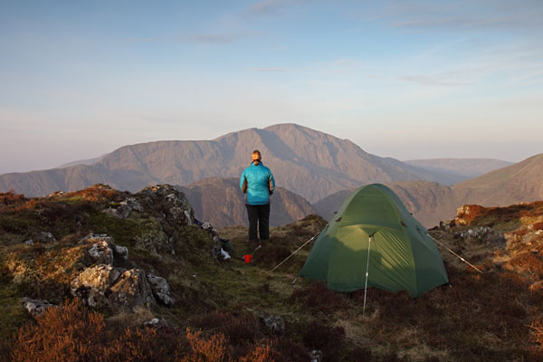 04D-5131 Hill Walker with Tent on Fleetwith Pike and the View Towards the Mountain of Pillar (Centre) in Early Morning Light Lake District Cumbria UK