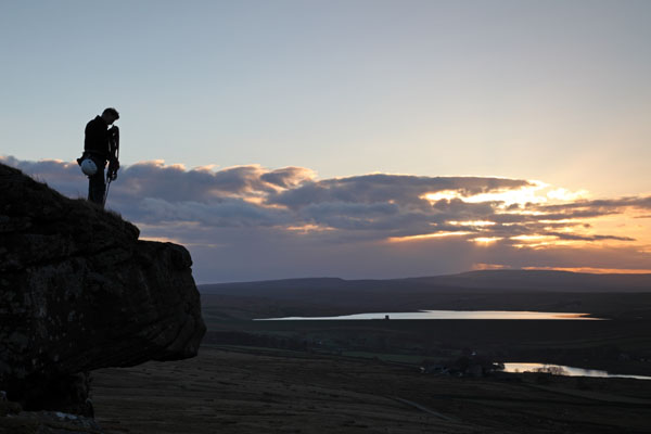 04D-7119 Rock Climber on Goldsborough Crag at Sunset with the Reservoirs of Balderhead and Blackton Behind Baldersdale Teesdale County Durham UK