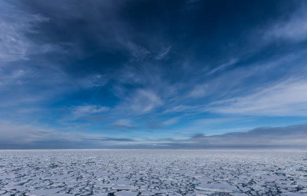 Blå lettskyet himmel og tynn is.