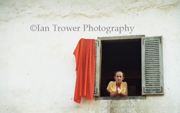 Monk Leaning Out Of Window, Phnom Penh, Cambodia