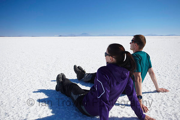 Couple sitting on Salar de Uyuni, Bolivia