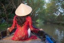 Woman wearing ao dai dress on canal, Can Tho, Vietnam