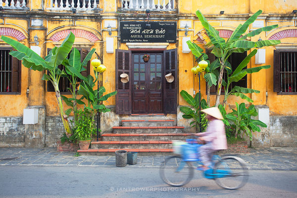 Woman cycling past restaurant, Hoi An