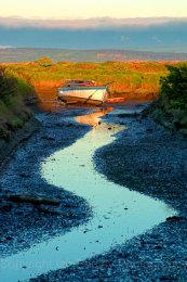 Lone yacht at low tide on Penngton Marsh, Lymington, Hampshire, England