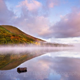 Still misty waters of Loweswater with trees in autumn colour, Lake District National Park, Cumbria, England