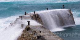 Rough seas crashing over the sea wall at Sennan Cove, Cornwall, England