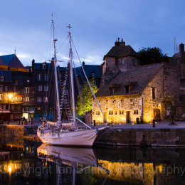 A classic sailing boat moored in the old port at Honfleur, France, at night
