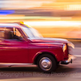 Red London taxi moving at night