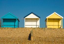 Three beach huts against a blue sky at Calshot, Hampshire, England
