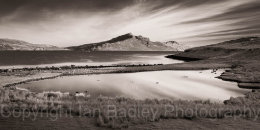 Sky streaks and view over pond and sea towards the Totternish Ridge, Isle of Skye, Scotland