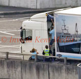 PICS SHOWS ;Channel Tunnel Large Security Operation . Illegal Immigrant is helped from his hiding place from on top of a lorry by the driver while the police officer looks on.