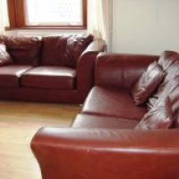 Leather sofas and laminate flooring in the lounge of 31 Storer Road, Loughborough student accommodation.