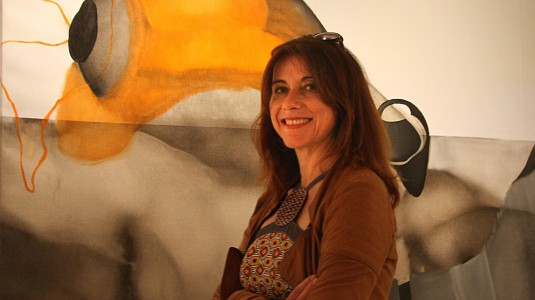 Artist Sonia Ros with one of her paintings