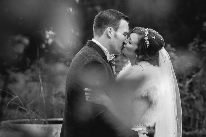 The bride and groom kiss in the grounds of the Wood Norton Hotel in Evesham after their winter wedding service. Wood Norton Wedding photography by Lee Webb