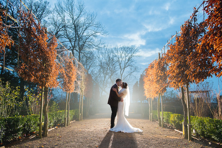A bride and groom kiss between two rows of trees in the grounds of the Wood Norton Hotel in Evesham after their wedding. Wood Norton wedding photography by Lee Webb