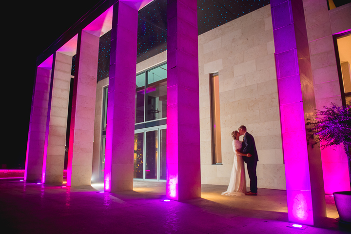 This wedding photo was captured at Stanbrook Abbey after the sun had set. The newly added dramatic lighting of Georges bar adds a fresh dimension to night time wedding photography at Stanbrook Abbey. Wedding Photography by Lee Webb