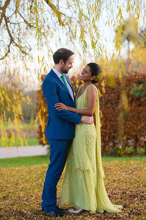 A bride and groom embrace under a golden yellow tree