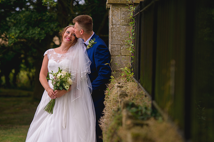 A groom kisses the bride on the forehead after their wedding at Honeybourne Church in Worcestershire