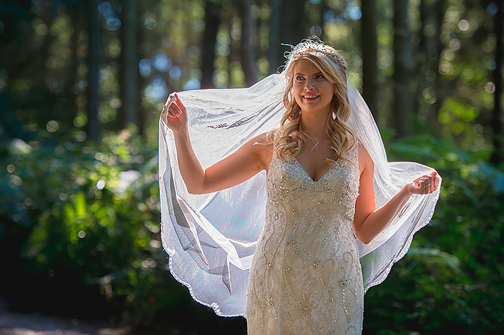 A bride holds her veil in the sunlight during her wedding at Wyre Forest in Worcestershire