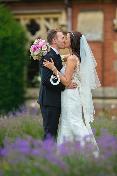 A bride and groom kiss after their wedding at Stanbrook Abbey in Worcestershire