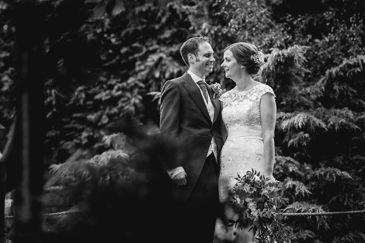 A bride and groom embrace in the rain at Redhouse Barn in Stoke Prior, Worcestershire
