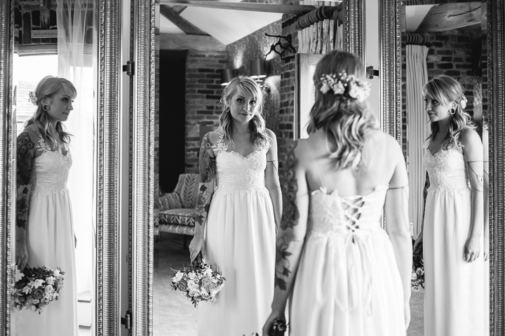 A bride looks at herself in the mirror moments before her wedding at Mythe Barn