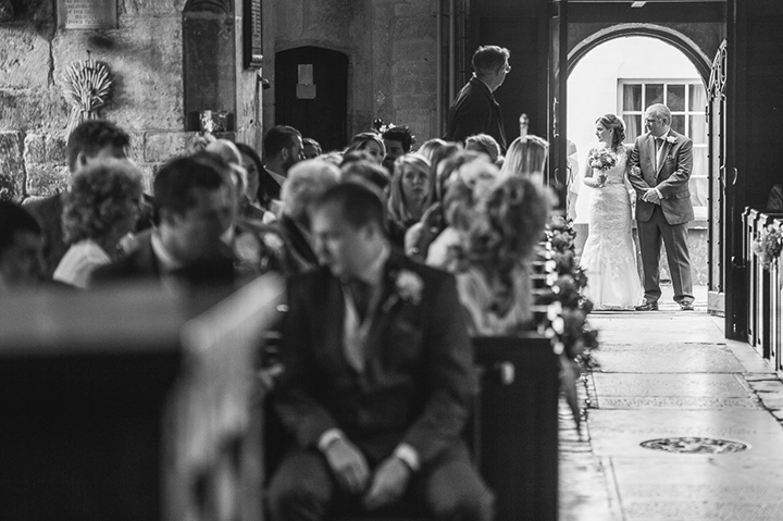 A bride and her father make their wait outside the church at Eckington, Worcestershire as the groom is being calmed by his best man. I love how much is going on in this wedding photo! Wedding photography by Lee Webb