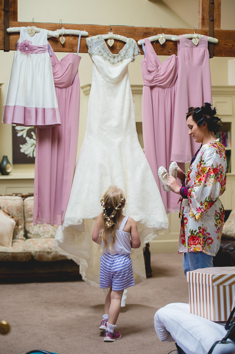 A bride and a young bridesmaid look at bridesmaid dresses and a wedding dress hung up in the cottage at Birtsmorton Court