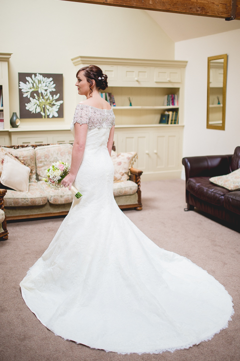 A Bride looks out of the window at Birtsmorton Court before her wedding