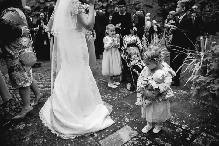Birtsmorton Court wedding photography. A young girl looks on in admiration at the bride's wedding dress during her wedding reception at Birtsmorton Court.