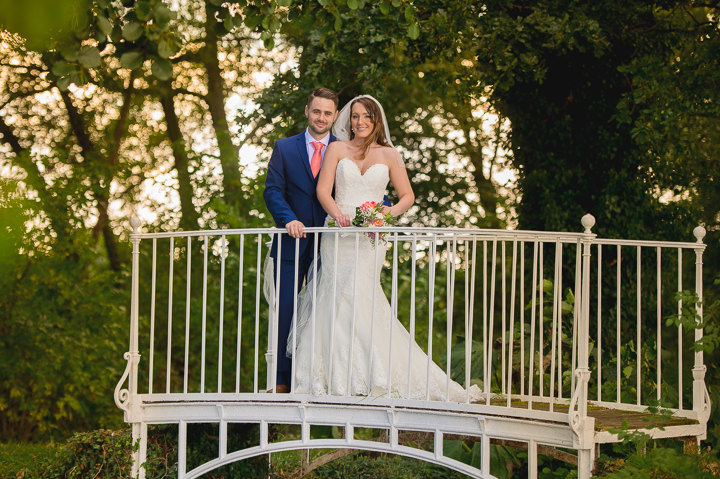 A bride and groom stand on the white bride at Birtsmorton Court in Worcestershire at sunset