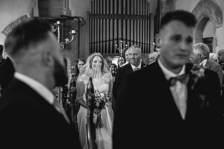 A bride walks down the aisle towards her emotional future husband at Honeybourne church in Worcestershire