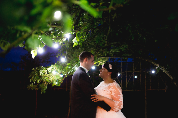 A bride and groom embrace under fairy lights at Redhouse Barn in Worcestershire