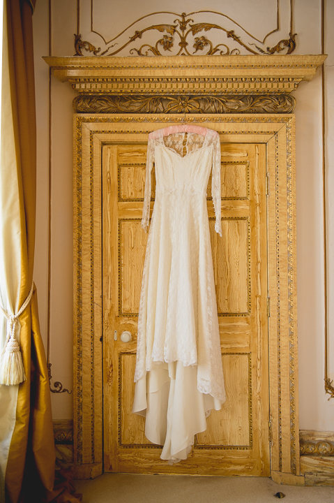 Beautiful wedding dress hanging from a door in the bridal suite at Gosfield Hall in Essex. Wedding photography by Lee Webb