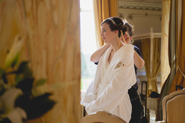 A bride has the final touches applied to her hair and tiara during her pre wedding preparations in the bridal suit of Gosfield Hall in Essex