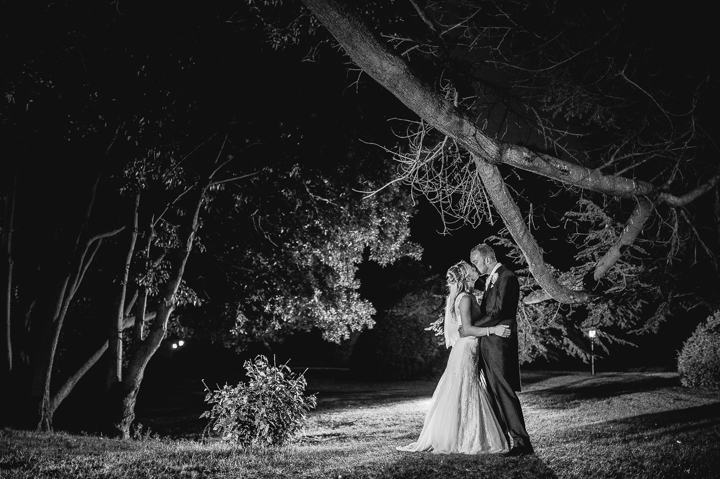 A bride and groom kiss in the grounds of Manor by the Lake in Cheltenham after their wedding. Manor by the Lake wedding photography by Lee Webb