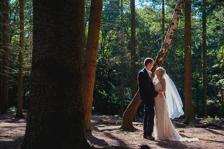 A bride and groom hold hands in the sunlight during their wedding at Wyre Forest in Worcestershire near Kidderminster